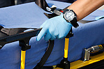 An EMT hand on a medical transport cot