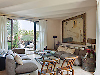 French windows open from the living room onto the front courtyard and are dressed with simple white curtains