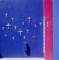 On an exterior wall the intense blue is used as the backdrop for a collection of antique crucifixes