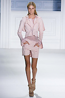 Kate Wagoner walks runway in a rose super pique long sleeve motorcycle jacket with zip hood over silk chiffon long sleeve eyelet top, and ose super pique skirted short by Vera Wang, for the Vera Wang Spring 2012 collection, during Mercedes-Benz Fashion Week Spring 2012.