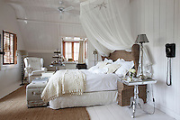 A ceiling fan, muslin canopy and wicker headboard lend an air of colonial romance to the master bedroom