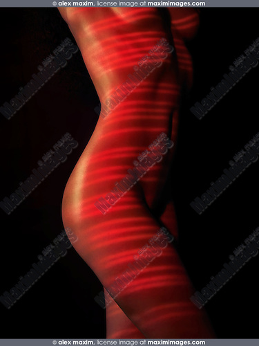 Nude woman body with red laser stripes on skin, isolated on black background