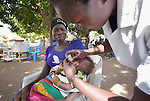 Estelle Agnes Astolo administers an oral vaccine to Nadia Misila's daughter Farida in Nimule, South Sudan, during a mobile clinic run by Caritas of the Diocese of Torit. The mobile clinic was launched in January 2014 shortly after war broke out within South Sudan, and thousands of families arrived in this area, near the country's border with Uganda, from Bor, in Jonglei State. Yet many have not been warmly welcomed to this region of Eastern Equatoria State, where two earlier waves of displaced people in the 1980s and 1990s left relations tense between the newcomers, who are Dinka, and the largely Ma'adi residents around the city of Nimule. The ACT Alliance is helping the displaced families and the host communities affected by their presence, and is supporting efforts to reconcile the two groups. The ACT Alliance also supports the Caritas mobile clinic, which provides medical care--often under a tree--both to displaced families as well as to poor residents of the host communities. Many of the newly arrived displaced families have not had their children vaccinated.