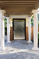 Columns lead to textured courtyard glass door