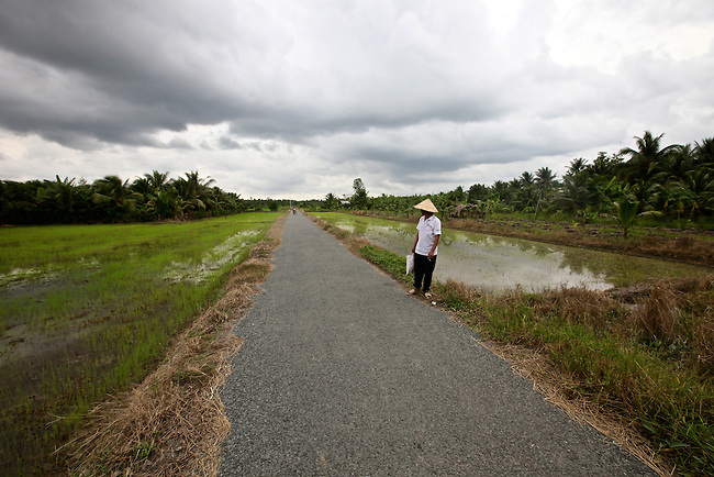 A man walks along a narrow country road in the Mekong Delta near My Tho, Vietnam. Oct. 3, 2011.