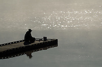 Man fishing from dock in early-morning fog