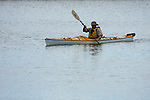 A male Kayaker kayaking in the harbor of Milwaukee Wisconsin in summer