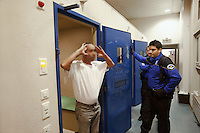 Switzerland. Geneva. A police officer is releasing an inmate from a cell at the Paquis police station. The arab man was arrested under the heavy influence of alcohol. A police station or station house is a building which serves for police officers. The building contains temporary holding cells and interview/interrogation rooms. Both policemen are wearing a ballistic vest, bulletproof vest or bullet-resistant vest which is an item of personal armor that helps absorb the impact from knives, firearm-fired projectiles and shrapnel from explosions, and is worn on the torso. Soft vests are made from many layers of woven or laminated fibers and can be capable of protecting the wearer from small-caliber handgun and shotgun projectiles, and small fragments from explosives such as hand grenades. 19.03.12 &copy; 2012 Didier Ruef