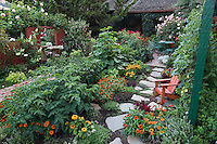 Orange chair in ornamental edible landscape with stepping stone path; cucumbers, peppers and 'Profusion Orange' zinnia flowers