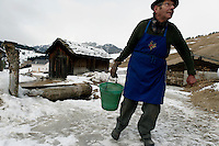 Lorenzo Miriboch carries water from the cattle trough because his pipes are frozen in La Valle. Lorenzo Miriboch lives alone in the Cianz district of the town.<br /> <br />  We knocked on his door and window for 20 minutes and finally a hand came across the curtain and a voice came out saying &quot;nobody home.&quot;  We then got a neighbor to bring him out and by the end of our stay he was kissing Melissa and wanting to bring us more Schnopps.