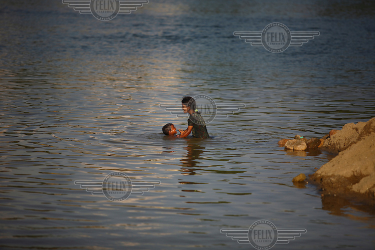 Children play in the Piyain river. At least 10,000 people, including 2,500 women and over 1,000 children, are engaged in stone and sand collection from the Bhollar Ghat on the banks of the Piyain river. Building materials such as stone and sand, and the cement which is made from it, are in short supply in Bangladesh, and commands a high price from building contractors. The average income is around 150 taka (less than 2 USD) a day.
