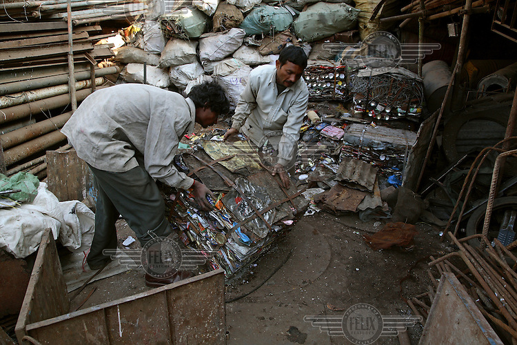 Scrap metal is compressed into bales by hand in a recycling yard.