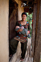 Nisha Darlami, 19, carries her 1 month old baby girl, Bushpa, as she stands at the door of her mother's house in Kalyan Village, Surkhet district, Western Nepal, on 30th June 2012. Nisha eloped with her step nephew when she was 13 but the couple used contraceptives for the next 6 years to delay pregnancy until she turned 18. In Surkhet, StC partners with Safer Society, a local NGO which advocates for child rights and against child marriage. Photo by Suzanne Lee for Save The Children UK