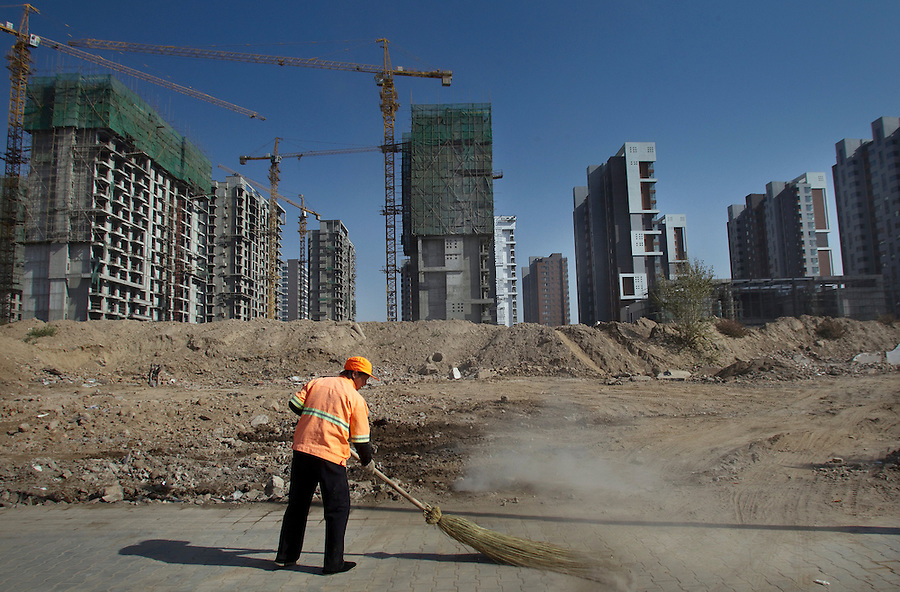 A worker sweeps dirt off a sidewalk near a huge residential construction site in the city of Linhe in Inner Mongolia. China could continue to add an annual 1,500-plus buildings that are more than 30 floors tall, equivalent to a new Chicago every year, resulting in more than 950 cities by 2030.