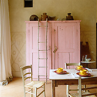 A large kitchen cupboard has been painted rose pink in contrast to the pale yellow ochre walls in this Italian kitchen