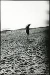 A young woman holding an umbrella walking along a sandy shore