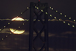 The Blue Moon hugs the Oakland Bay Bridge in San Francisco, California.