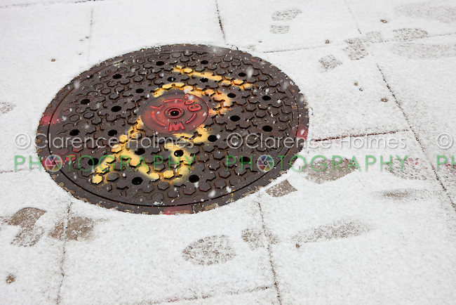 A manhole on a snowy sidewalk in White Plains, New York, USA