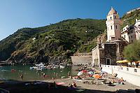 Sun bathers in the small port of Vernazza, Cinque Terre, Liguria, Italy