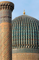Detail of dome and minaret, Gur-Emir Mausoleum, 1417-20, Samarkand, Uzbekistan, pictured on July 15, 2010, at dawn. Gur-Emir Mausoleum, or Tomb of the Ruler, was built by Timur in 1404 for his favourite grandson, Mohammed Sultan, and became the mausoleum for the Timurid dynasty. The simply formed building is an octagonal drum beneath an azure fluted dome (diameter: 15m, height: 12.5m). Its walls are tiled in blue and white geometric and epigraphic patterns including the words 'God is Immortal' in 3m. high white Kufic script around the top of the drum. Samarkand, a city on the Silk Road, founded as Afrosiab in the 7th century BC, is a meeting point for the world's cultures. Its most important development was in the Timurid period, 14th to 15th centuries. Picture by Manuel Cohen.
