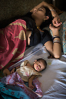 A mother with her newborn baby in the labour ward of Shivpuri District Hospital. A shortage of beds in this under-resourced hospital means many must share or are forced into the corridor. Like many of India's public hospitals, this facility is over subscribed and under resourced. ..Shivpuri district in Madhya Pradesh suffers from poor health outcomes. Of particular concern is the high rate of maternal mortality. One of the Indian government's aims, with partners Unicef, is to encourage the population to adopt practices to improve sanitation and health practices. In an area made up of traditionally disadvantage groups and suffering low literacy rates, this can be a challenge. ..A survey found that radio was the most readily accessible media by the Shivpuri community with more than half saying they tuned in several times a day. ..Dharkan 107.8 FM will go on air in July. The station that will broadcast to 75 villages in a 15-kilometer radius reaching 170,000 people...Rather than preaching educational messages, the station, which is already producing pilot programs, uses humor and folk artists performing in the local language to entertain and inform their audiences. There is a major impact, especially on women, who are contributing their voices to such wide-ranging issues as caste discrimination, female feticide and women,A?o?s empowerment. ..Photo: Tom Pietrasik.Shivpuri, Madhya Pradeh. India.June 2009