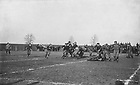"GATH 19/01:  Football Game Scene - ND vs. Wabash, 1909/1120.  Offensive play including Harry (Red) Miller, William Schmitt, Joe Collins, George Philbrook, Al (Red) Kelly, Luke Kelly, Don Hamilton, Sam ""Rosey"" Dolan, Howard (Cap) Edwards, Ed Lynch..Image from the University of Notre Dame Archives."