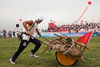A competitor dressed as a revolutionary farmer pushes a wheel barrow on the 'battlefield' at the Red Games. Held in Junan County, this sporting event is a nostalgic tribute to the communist era.