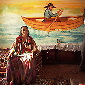 "An elder Roma woman, Sibinca,  sits on a bed infront of a nautical scene, depicting a ""pilgrim boatman"" painted on the wall of her home, in the new part of the Sintesti Roma camp. Nautical scenes are very popular as wall decoration, but no-one within the camp knows the reason why they were first painted."