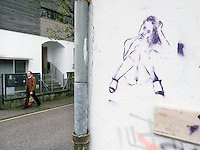 Switzerland. Canton Ticino. Lugano. A man wlaks on a side walk and passes by a graffiti on a wall of a naked woman. 29.04.13 © 2013 Didier Ruef