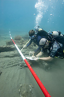 Two SCUBA divers sketch a 17th century shipwreck in Panama. (Model Released)