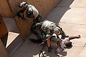 "17th Iraqi Division soldiers search an armed ""insurgent""  after mock shooting him during training exercises August 30, 2010 at the Joint Security Station (JSS) Deason in Mahmoudiyah, Iraq."