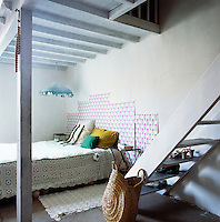 The bedroom has a simple, rustic feel with its painted roof beams and stone floor