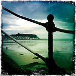 Iron railings leading down to beach with tide out and couple walking along the sandy beach, headland in distance with buildings in England