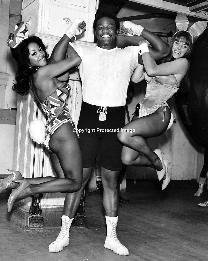 Heavyweight champ George Foreman with Playboy bunnies. (photo by Ron Riesterer)