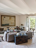 A pair of brown comfortable sofas and a large mixed media artwork in the living room