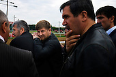 """Chechen President Ramzan Kadyrov leans on his bodyguard while he attends a horse race in Moscow's Hippodrome..Kadyrov's horse, """"Royal Quiet"""", came first in the 1600-metre race. .The horse, born in the U.S.A., is parented by father: Real Quiet, mother: Dinasoar, is trained by S. G. Kolesnikov and rode by master jockey S. V. Petin.."""