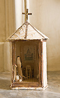 A small model chapel made of papier mache with a nun at prayer