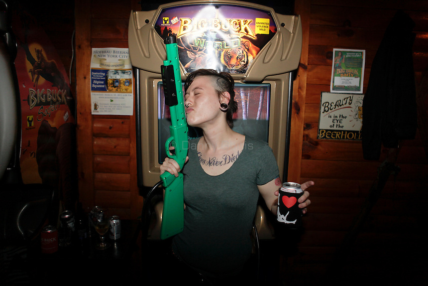 """Emily Star, 24, who is a vegan, poses for a portrait at The Black Bear Lodge in Manhattan, which hosted an official Big Buck Party on Thursday April, 28, 2011. She said it does not bother her to shoot animals in the game because she is """"not actually blowing bunnies heads off.""""  Fans of the popular hunting arcade game were invited to test their skill against other Big Buck Hunter fans to compete for prizes, enter to win raffle merchandise and meet Big Buck Girls...Danny Ghitis for The New York Times"""