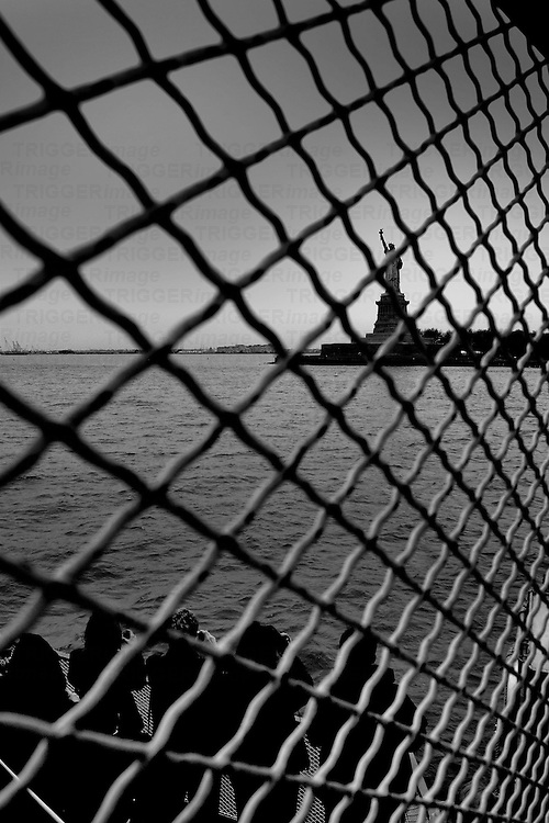 Overcast daylight shot of the Statue of Liberty through a fence from a boat on the Hudson River. people in the foreground.