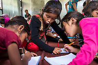 Children help each other as they write lines in their notebooks learning basic english in the SOS Children's Villages Child Care Space in Rayale, Nepal on 1 July 2015. The Child Care Space was set up by SOS Children's Villages soon after the earthquake so that they children of the village can come together to play, learn, and get over the trauma of the disaster, while their parents can be free to reconstruct their homes and go off to get rations and relief kits. Photo by Suzanne Lee for SOS Children's Villages