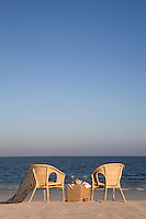 A pair of wicker chairs on the beach looking out to sea