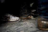 Muddy feet of illegal immigrants who, after crossing the Turkish-Greek border, have been detained by officers of the EU border police, Frontex. According to UNHCR, 38,992 immigrants arrived in Greece in the first 10 months of 2010, whereas in 2009 the number was only 7,574. A poster in the window shows prices to travel to Athens. According to Frontex, around 245 people tried to cross the border illegally every night during October.