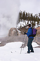 Cross-country skier watching eruption at Lone Star Geyser; Yellowstone National Park.