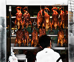 Peking ducks hang in a window display in Shenzhen.