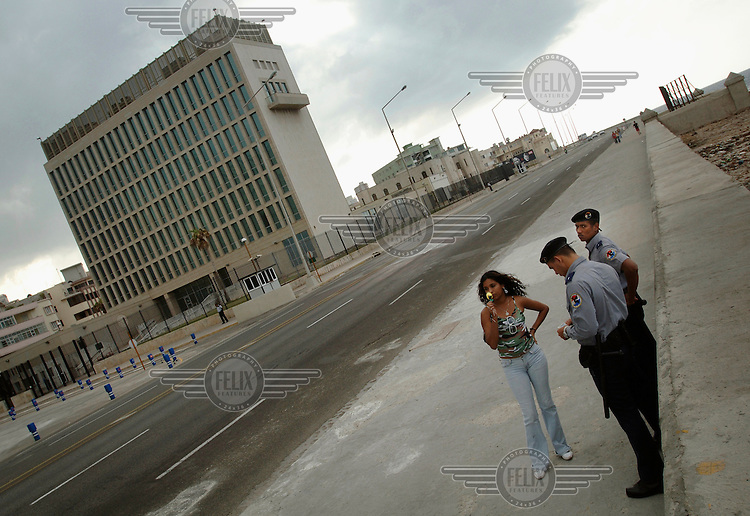 Police check the identity (ID) papers of a girl outside the U.S. Interests Section (USINT) building, the de facto U.S. embassy, on the Malecon.