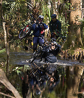SwampStomp at the Chassahowitzka.  Jason Lazzaro (front, bike above head), Clay Bentley (left, bike on shoulder) and Costa Wallace (right) make their way through swamp water during the 2010 WeCeFAR (West Central Florida Adventure Racing) Swamp Stomp 30-Hour Adventure Race and Son of Swamp Stomp 6-8 Hour Challenge which began and ended at the Chassahowitzka National Wildlife Refuge.