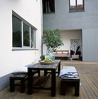 A wooden table and bench seats are set out on a paved terrace area