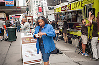 Olive Garden fans and the curious line up at the Olive Garden truck outside of Penn Station in New York to sample the casual dining restaurant's new offering, the Breadstick Bun Sandwich, on Friday, June 5, 2015. Olive Garden has been making changes to its menu in an effort to reverse the slump that is effecting casual dining restaurants. Recently, the board members of the company worked greeting and serving guests to gain hands-on experience. (© Richard B. Levine)