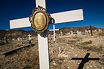 Photo in small glass frame on wooden cross at the Historic early 1900s cemetery, Goldfield, Nev..