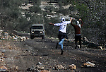 Palestinian protesters throw stones at Israeli security forces as clashes broke out during a demonstration against the expropriation of Palestinian land by Israel in the village of Kfar Qaddum, near the occupied West Bank city of Nablus, on Jan. 31, 2014. Photo by Nedal Eshtayah